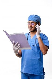 젊은 인도 의사는 일부 보고서를 확인하고 스마트폰으로 이야기합니다.