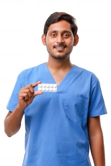 Young indian doctor holding pill in hand.