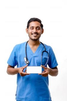 白い背景の上にスマートフォンの画面を表示している若いインドの医師。