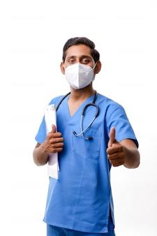 Молодой индийский доктор с блокнотом стетоскопа и показывая большие пальцы руки вверх над белой предпосылкой.