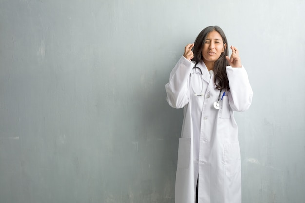 Young indian doctor woman against a wall crossing his fingers