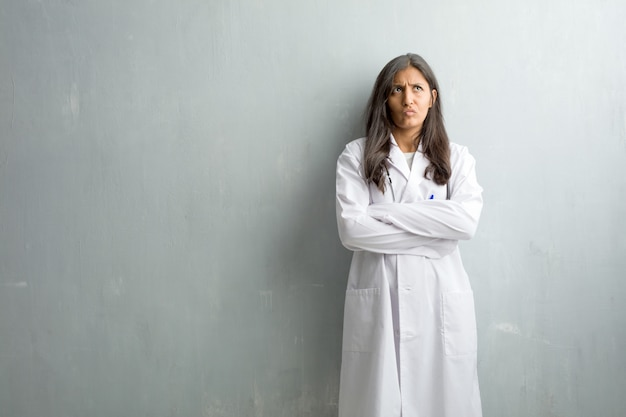 Young indian doctor woman against a wall doubting and confused