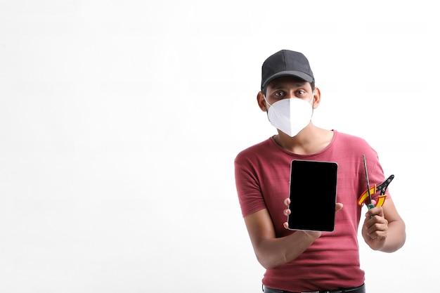 Молодой индийский электрик, держа в руке инструменты и показывая смартфон.