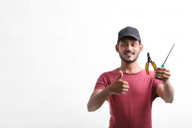 Молодой индийский электрик, держа в руке инструменты и стоя на белом фоне.
