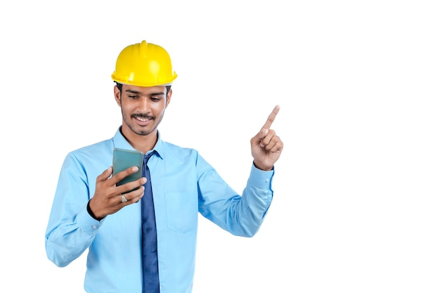 Young indian engineer or construction site worker using smartphone.