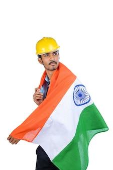 노란색 모자를 쓰고 국기를 흔드는 젊은 인도 엔지니어.