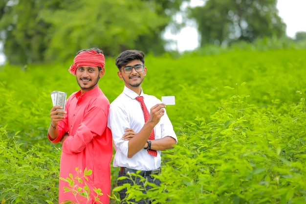 若いインドの農夫と銀行家がお金とカードを見せて