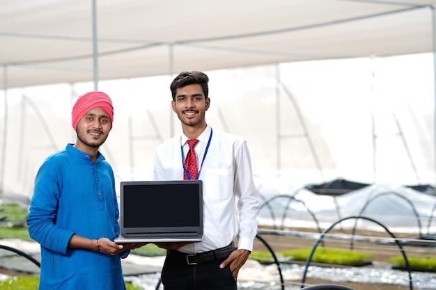 温室で若いインドの農民と農学者のラップトップ画面