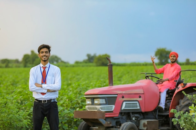 Молодой индийский фермер и банковский служащий с новым трактором на сельскохозяйственном поле