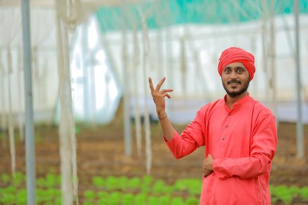 온실 또는 폴리 하우스에서 젊은 인도 농부