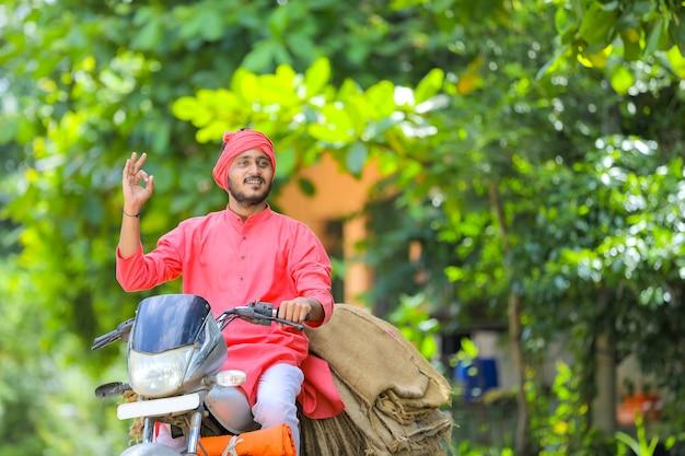 Young indian farmer collect sackcloth bag on motor bike