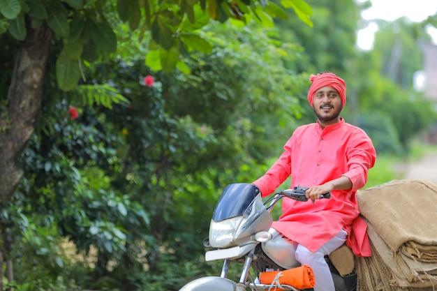 若いインドの農民はバイクで荒布袋を収集します