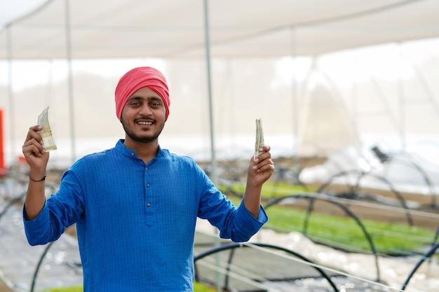 温室でお金を数えて見せている若いインドの農夫
