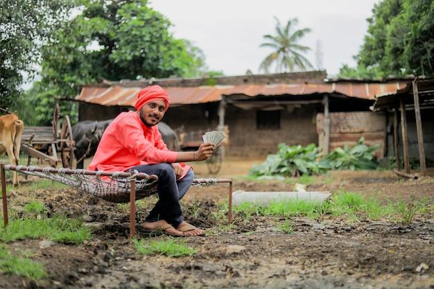 お金を数えて見せている若いインドの農夫