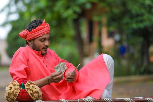 Молодой индийский фермер считает деньги дома