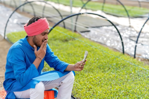 Young indian farmer counting and showing money at greenhouse