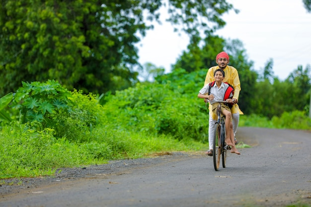 Young indian farmer and his son going to school on cycle