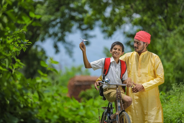Young indian farmer and his son going to school