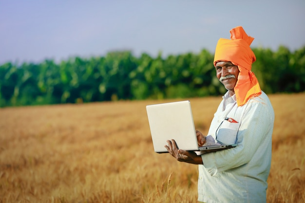 Young indian farmer in his wheat field