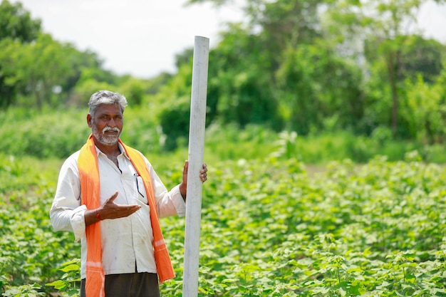 Young indian farmer holding pipe at cotton field.