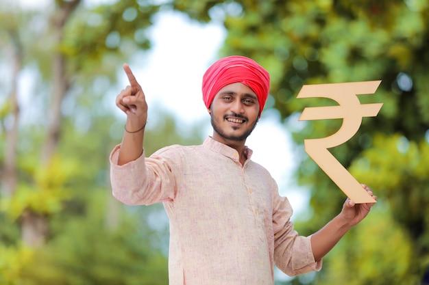 手にルピー記号を保持している若いインドの農民。