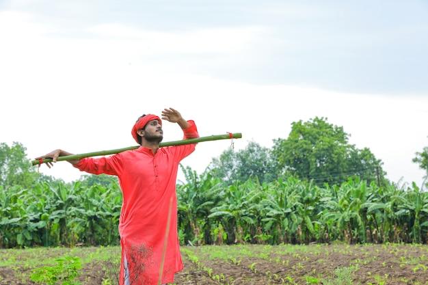 フィールドで伝統的な衣装を着た若いインドの農夫