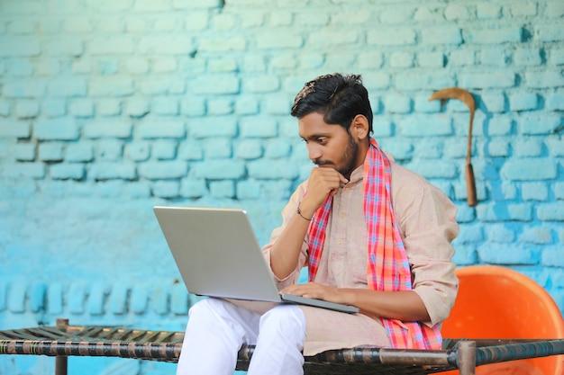 ラップトップでいくつかの詳細を見た後、うつ病の若いインドの農民。