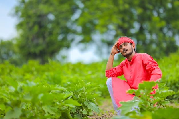 Молодой индийский фермер в стрессе или думает в поле баклажанов