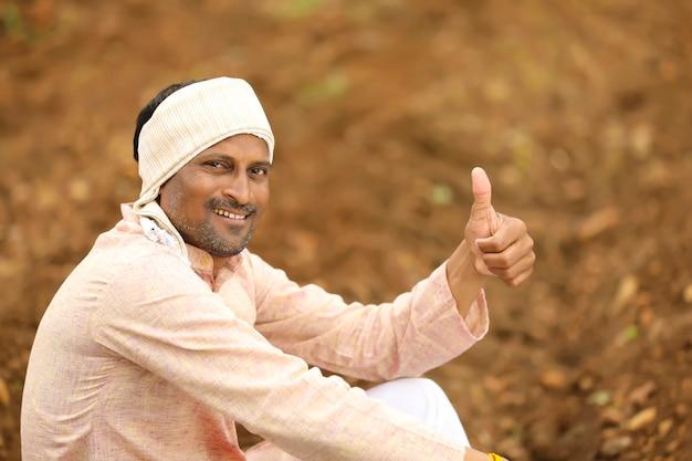 伝統的な服を着て、野外でゴツゴツした若いインドの農民。