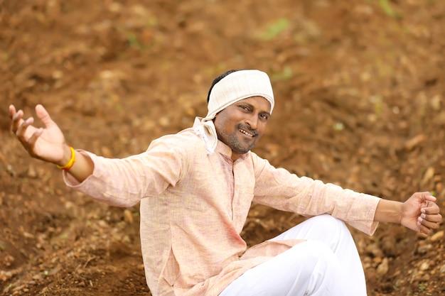 伝統的な服装で農業分野に座っている若いインドの農民。