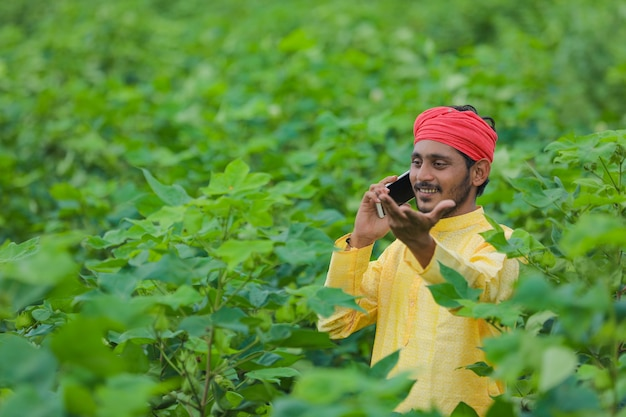 Young indian farmer or labor talking on mobile phone at cotton field