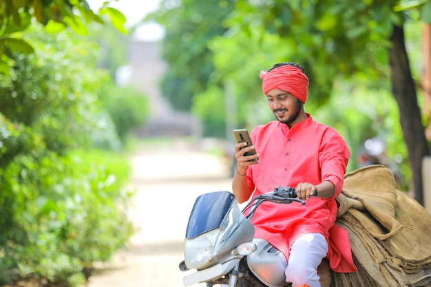 Young indian farmer on motor bike and using smart phone