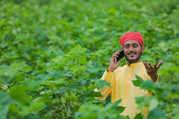 綿花畑で携帯電話で話している若いインドの農民または労働者