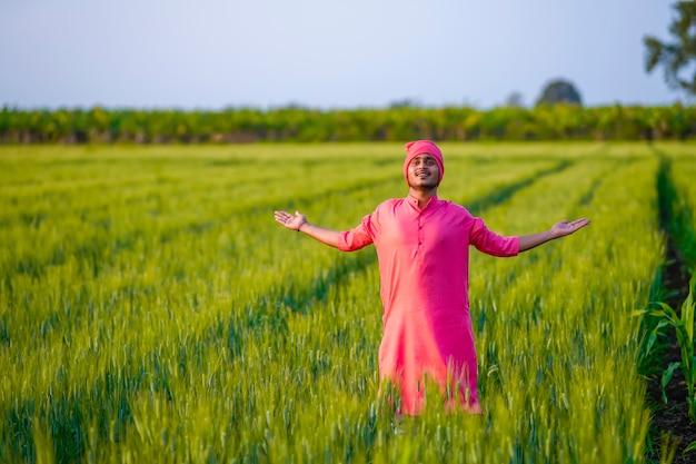 若いインドの農民が手を挙げて、緑の麦畑で自然を楽しんでいます