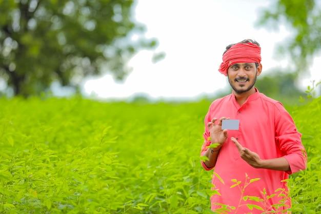 Молодой индийский фермер показывает карту на зеленом поле