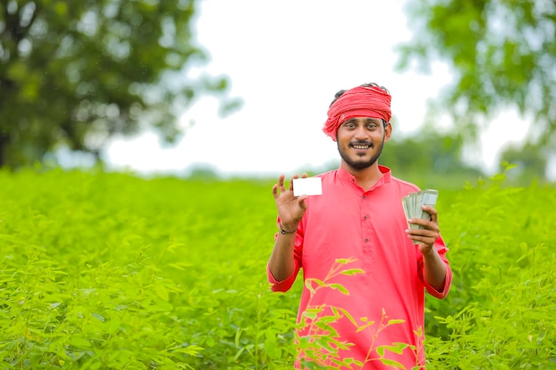 Young indian farmer showing card at green field
