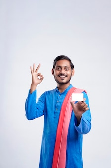 흰색 바탕에 카드를 보여주는 젊은 인도 농부