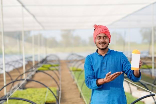 온실에서 비료 병을 보여주는 젊은 인도 농부