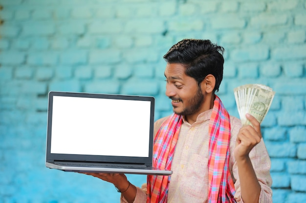 Young indian farmer showing laptop screen and money