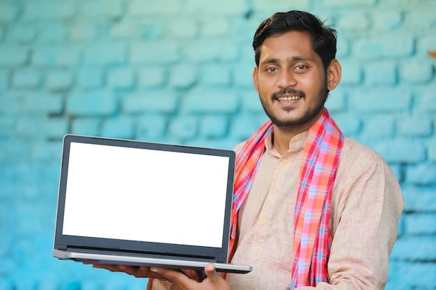Young indian farmer showing laptop screen.