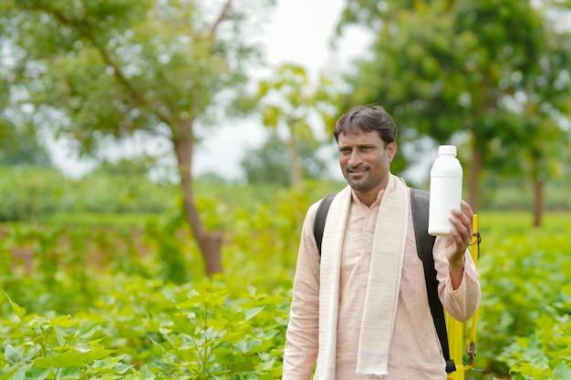 農業分野で液体肥料のボトルを示す若いインドの農民。