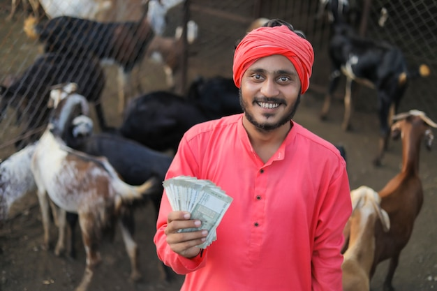 Young indian farmer showing money at goat dairy farm