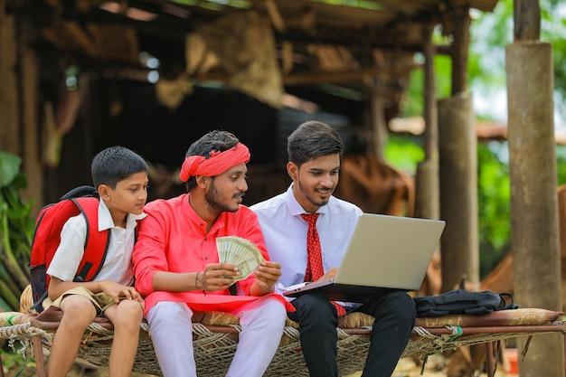 家で農学者や銀行家とお金を示す若いインドの農民
