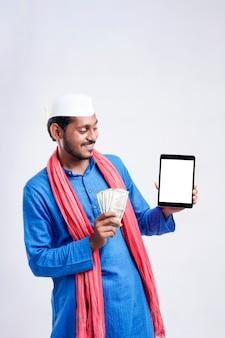 白い背景の上のスマートフォンとお金を示す若いインドの農民。