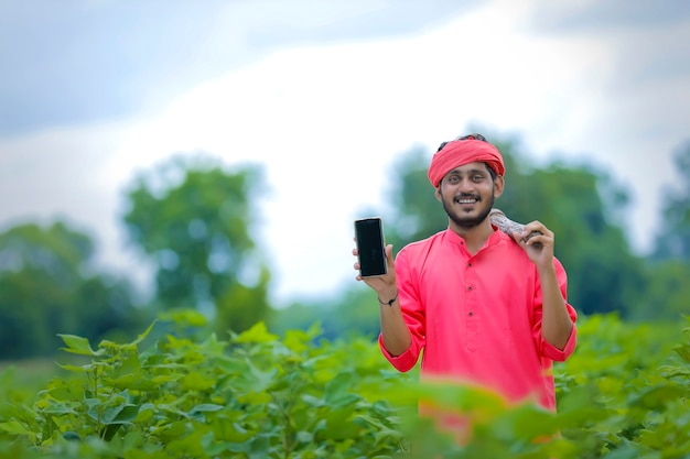Young indian farmer showing smartphone in green cotton field