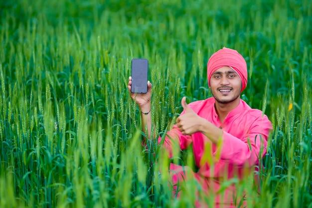 밀밭에 스마트 폰 화면을 보여주는 젊은 인도 농부