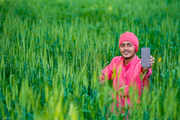 小麦畑でスマートフォンの画面を表示する若いインドの農民