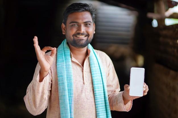 スマートフォンの画面を表示している若いインドの農民