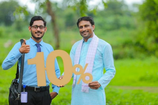 그의 가축 농장에서 경제학자 또는 금융가와 함께 10% 기호를 보여주는 젊은 인도 농부