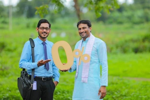 그의 농장에서 농업 경제학자나 금융가와 함께 0퍼센트 기호를 보여주는 젊은 인도 농부.